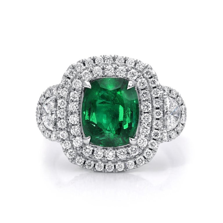 Emerald ring hand set with a cushion cut weighing 2.77 carats, adorned by a total of 1.43 carats of micro pave diamonds. This Emerald engagement ring or Emerald cocktail ring is crafted in 18K white gold. Size 6.5. Re-sizing is complimentary upon