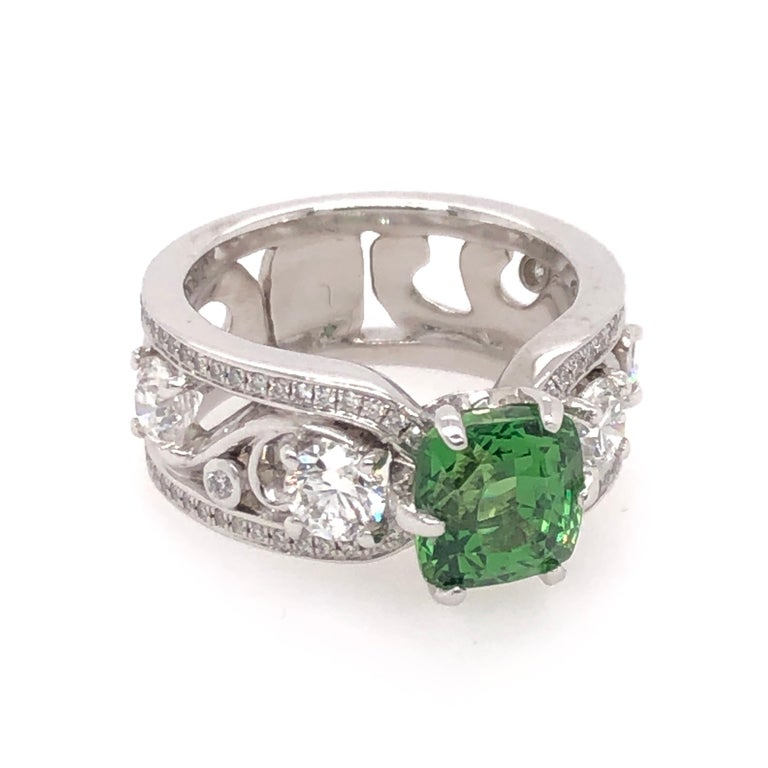 This radiant cushion cut 2.52CT green tsavorite crowns its floral motif 18K white gold setting. A total of 1.65 CTS of round cut diamonds brighten the ring with the right amount of sparkle to accent the freshness of the green tsavorite.    Size: 5