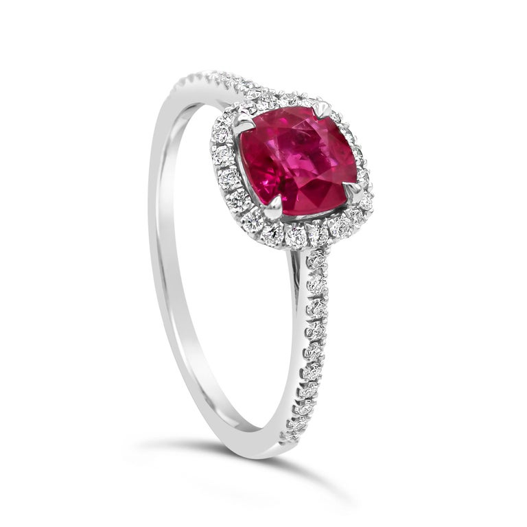Showcases a cushion cut ruby weighing 1.11 carats, surrounded by a single row of round brilliant diamonds in a seamless halo design. Set in a thin 18 karat white gold band accented with diamonds. Diamonds weigh 0.24 carats total.  Style available in