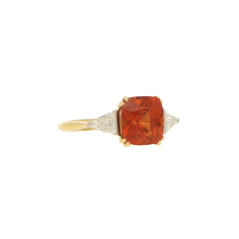 A fabulous spessarite garnet and diamond engagement / dress ring set in 18k yellow and white gold.  The ring is centrally set with a beautiful cushion cut spessarite garnet which is four claw set to centre. This garnet is then sided by two
