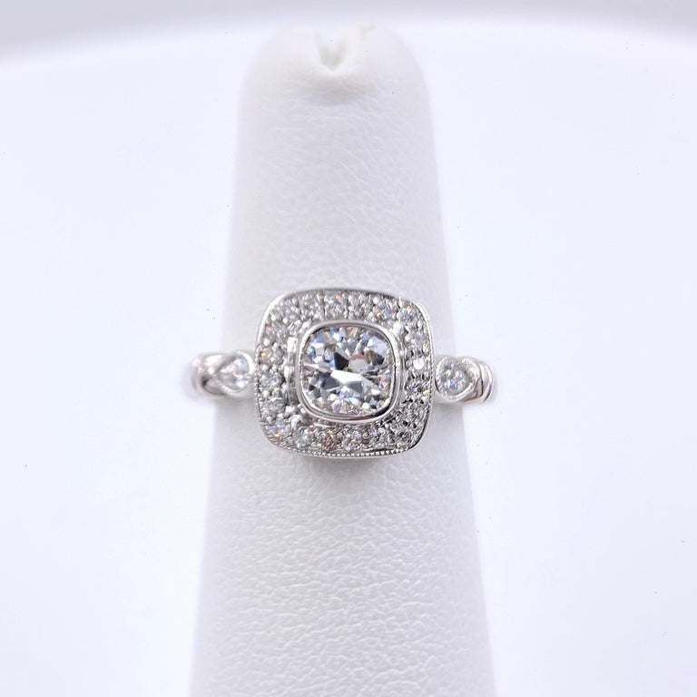 Diamond Engagement Ring Style:  Bezel Set with Halo Ring Metal:  18kt White Gold Size:  6 - sizable TCW:  1.20 tcw Main Diamond:  Cushion Diamond 0.70 cts Color & Clarity:  G - VS2 Accent Diamonds:  38 Round Brilliant Cut 0.40 tcw  G-H VS2-SI1 & 2