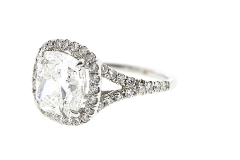 This cushion diamond halo engagement ring features a 1.74 F SI1 GIA certified cushion center diamond and is surrounded by a diamond halo and diamonds on the shank for a total carat weight of 2.31 in a 14K white gold setting.