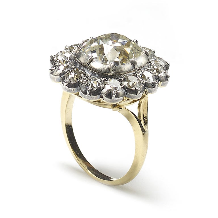 A diamond cluster ring, set with a 4.18ct, J colour, VS2 clarity, cushion shaped, old-cut diamond, surrounded by fourteen, old-cut diamonds, with an approximate total weight of 2.26ct, in cut down settings, mounted in silver-upon-gold, accompanied