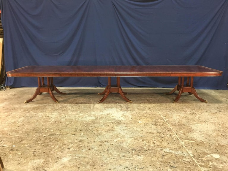 This is a made-to-order large traditional mahogany banquet/dining table made in the Leighton Hall shop. It features a field of slip-matched swirly crotch mahogany from west Africa and satinwood and santos rosewood borders from South America. It has