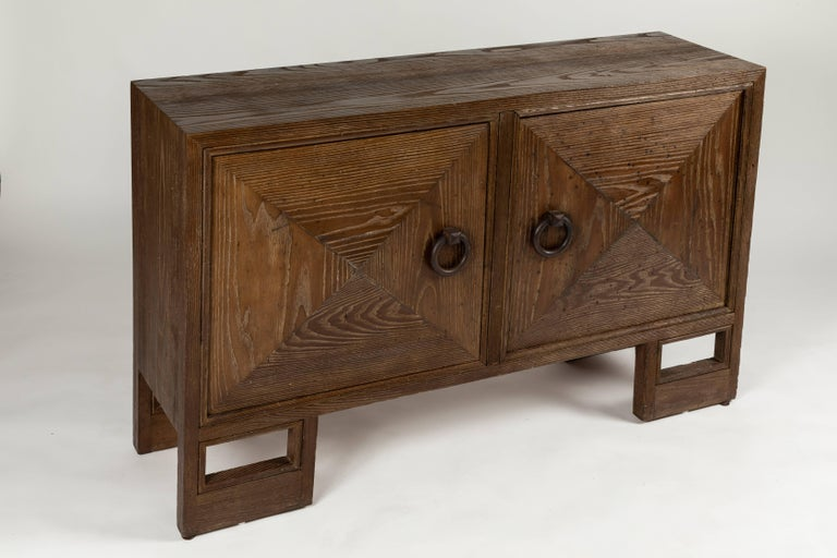 A rare and early two-door cabinet designed by James Mont. The original finish to the open grained oak is a rich smoke color. I believe the finish is original as there are no signs of refinishing... The trapezoidal cabinet is branded on the inside
