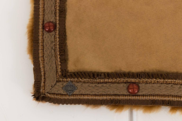 Contemporary alpaca throw blanket with faux suede lining and leather trim with metal stud details.