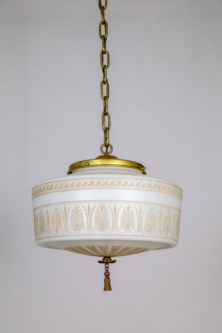 Antique, French milk glass, circa 1910, with painted, tan, neoclassical decorations of curved wave lotus and acanthus leaves. A new, custom, fixture with long chain, and rose patina on brass shade holder and canopy, and painted, metal tassel finial.