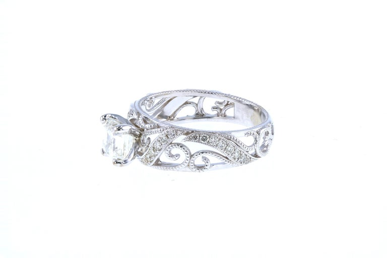 This diamond ring is crafted in 18k white gold, contains an Asscher Cut Diamond (1.12 total carat weight, H color, VS1 clarity) and is surrounded by 28 Round Brilliant Cut Diamonds (0.25 total carat weight, H color, VS clarity).  Stunning in detail,