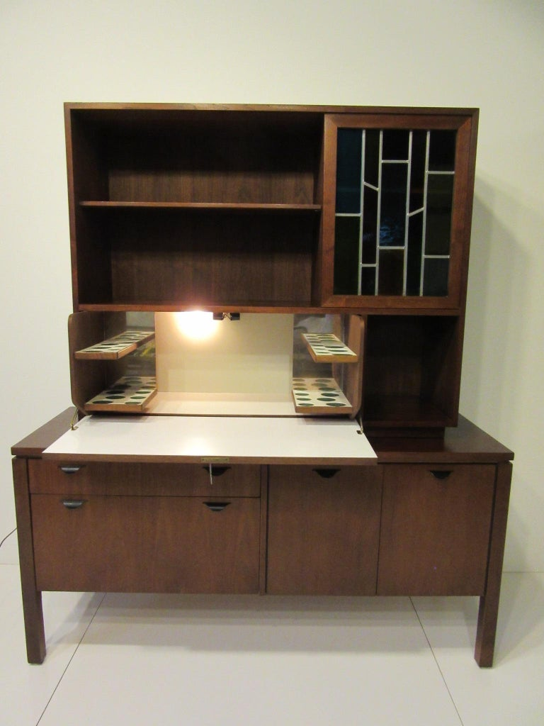 A two-piece custom bar cabinet with pull down door revealing a light up space in white laminate for glasses and bottles having the original key for the lock. The upper cabinet has two adjustable shelves, storage and a sliding stain glass door, the