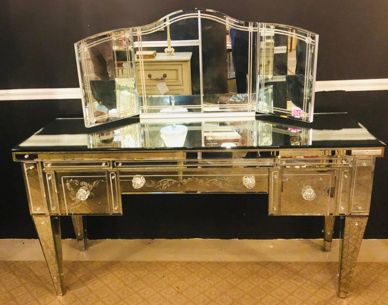 Hollywood Regency beveled and etched glass mirrored vanity desk. Finished on all sides, lined interior having a tri-fold desk top etched mirror measuring: 48 inches wide by 21 inches high. This simply stunning custom made beveled mirror etched glass