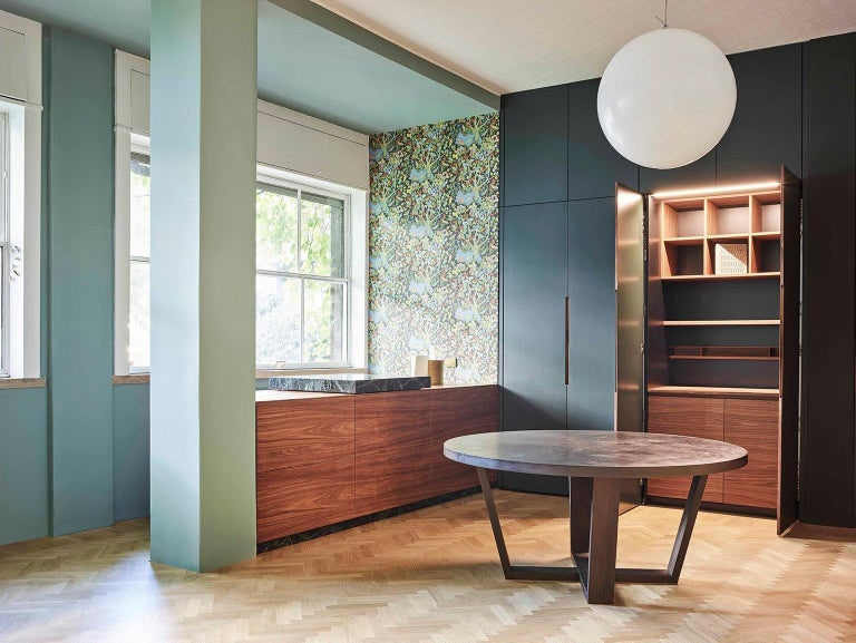 Equipped wall unit with extra-matte lacquered doors and work station with hidden doors. Peninsula in American walnut with sliding cutting board in green alpi marble that unveils a cooktop with integrated hood. Cutlery tray in solid walnut.
