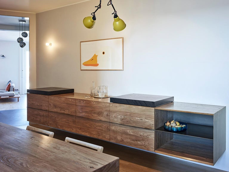 Kitchen with fossil elm finished transparent matt suspended volume. Sliding ocean black cutting boards.