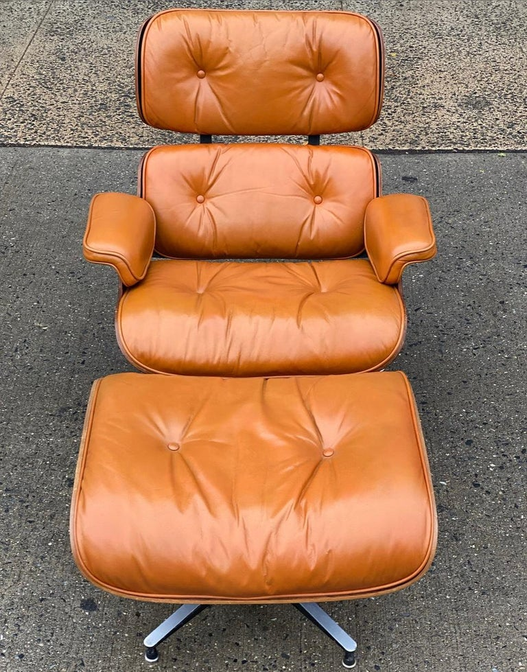 Beautiful custom edition of the iconic Eames lounge chair and ottoman. Rosewood shells and aluminum bases cradle the custom burnt orange leather cushions. Leather very soft and in excellent condition with minimal signs of use. This color is