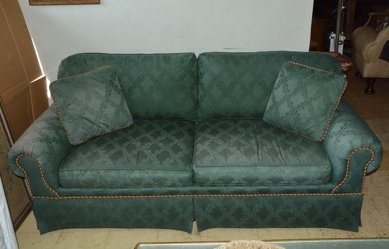 Two-seat upholstered sofa featuring classic English style rolled arm design. Upholstered and completely skirted on all sides this sofa was made by Kravet one of the finest furniture makers in the country. Upholstery is faded on the right arm
