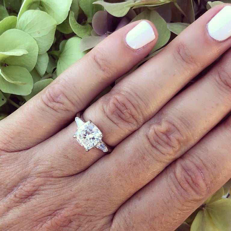 Exceptionally stunning 3.01 carat square-shaped cushion-cut diamond engagement ring, F color and VS1 clarity, set in a platinum mounting, with a bullet-shaped diamond on either side, with a 3.31 total weight for the ring. Unique and eye-catching!