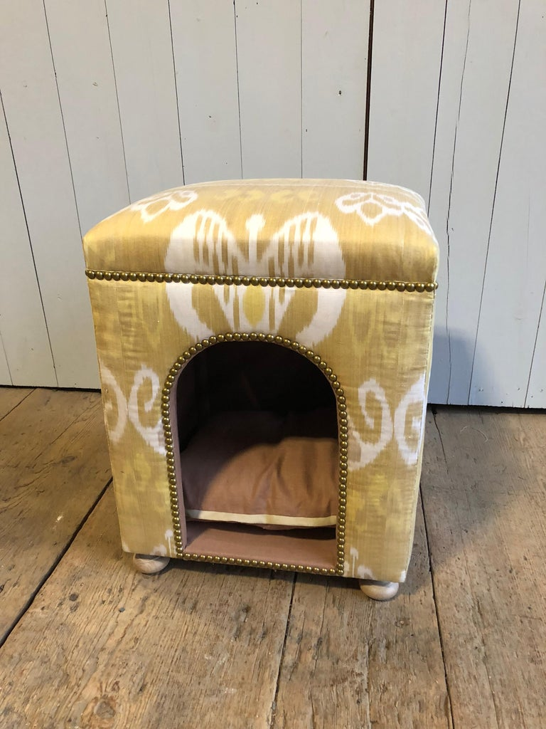 A custom dog bed upholstered in handwoven silk Ikat fabric, the top padded and at seat height to double as a stool. Brass decorative nailheads and turned wood feet.