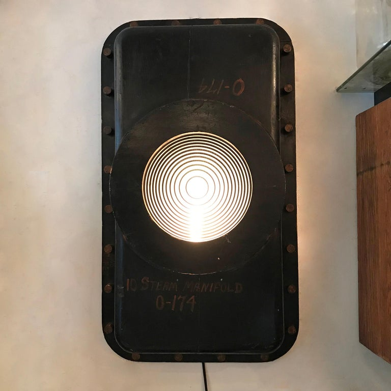 Large-scale, custom, industrial wall sconce light features a 1930s foundry pattern surround with Fresnel lens shade that is wired to accept up to a 150 watt bulb.