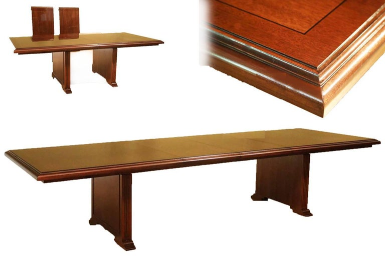 This is a made-to-order mahogany conference table made in the Leighton Hall shop. It features a field of cathedral mahogany with a contrasting mahogany border and a solid mahogany edge. It has two