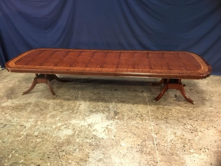 This is a made-to-order large traditional mahogany banquet/dining table made in the Leighton Hall shop. It features a classic scallop corner design with a field of slip-matched swirly crotch mahogany from west Africa and tulipwood, satinwood and