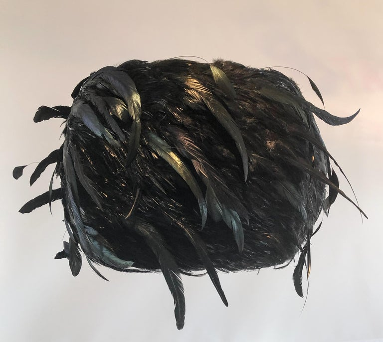 A whimsical one of a kind lampshade using black coque hackle pads combined with longer stripped coque feathers. The feathers are layered and glued on to a silk shade with a sturdy metal armature.   These shades are custom made and we are pleased to