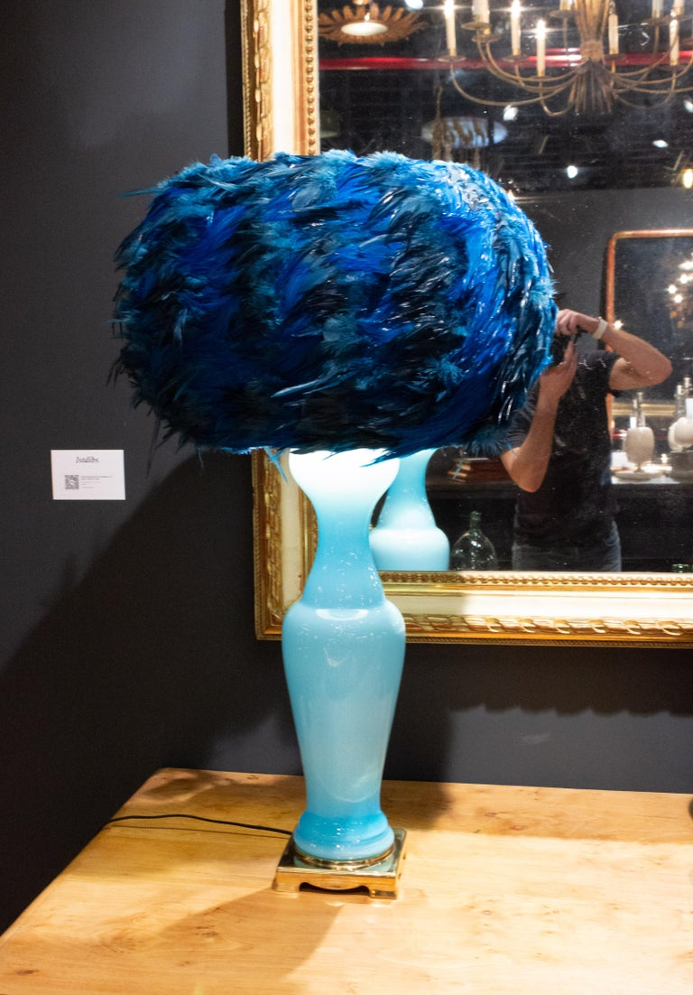A whimsical one of a kind lampshade using dyed toque feathers that are layered and glued on to a silk shade with a sturdy metal armature. These shades are custom made and we are pleased to work closely with you in designing the perfect shade for