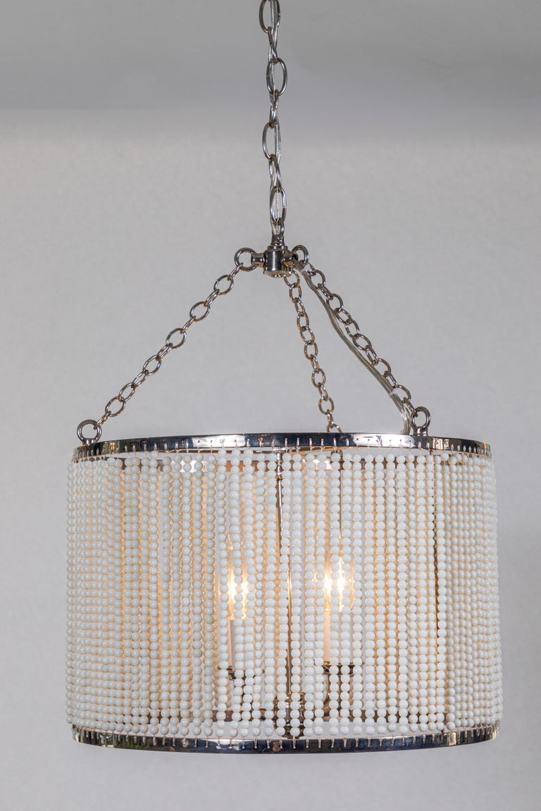 Custom made hanging polished nickel drum pendant light with strung white glass bead detailing.