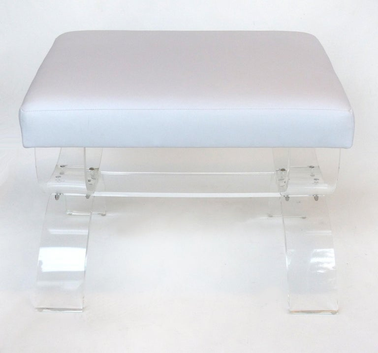 Offered for sale is a rectangular Lucite bench with curved X-form legs and an upholstered seat cushion. This is a new prototype and is available in other sizes and your choice of fabric. The seat is covered in a white soft faux-leather upholstery