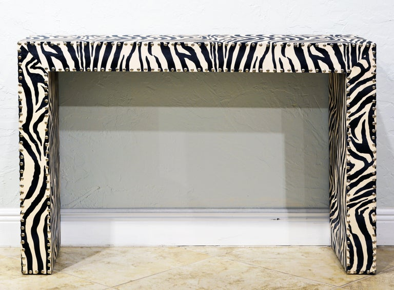 The design and proportions of this vintage Mid-Century Modern console table are strictly modern and Minimalist. It is covered in a spill proof faux zebra print on all sides including the underside and trimmed with shiny chrome nailheads along edges.