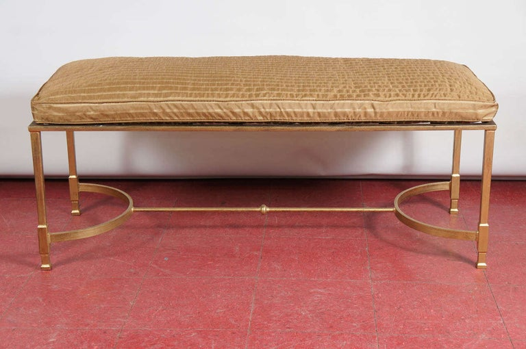 This neoclassical style metal bench or stool with two curves and stretcher in between can be used for various seating purposes or at the foot of a bed. The base topped with a piece of glass, stone or wood can serve as a coffee table. Cushion can be
