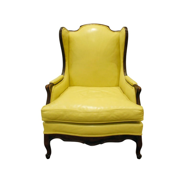 """Regency style wing chair with carved arms and legs and original yellow faux leather upholstery by Mason-Art, American, 1950s (signed with original label """"Mason-Art—Custom-Made"""" on the underside of the cushion)."""