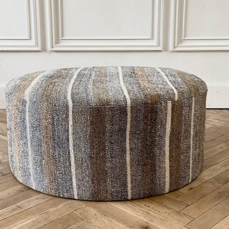 Custom made vintage Turkish rug round cocktail ottoman coffee table  Measures: 41? round x 17? height  Once a stripe rug now a useful cocktail ottoman. Wool and goat hair rug in a greyish, brown, golden tones with white woven striped