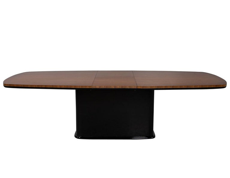 Carrocel custom Mid-Century Modern inspired dining table. Featuring rectangular pedestal with rift cut vertical walnut and bottom molding in black. Finished in a natural walnut satin flat finish. This table has a butterfly leaf that can be stored in