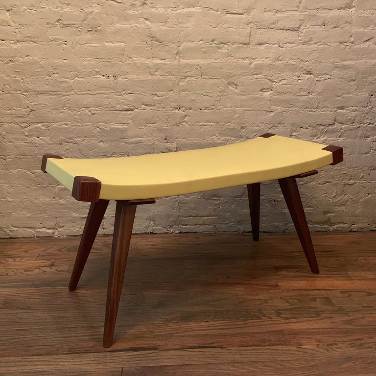 Custom, Mid-Century Modern style bench features walnut and ash tapered legs with a gently sloping, yellow leather seat, made in Brooklyn, NY by City Foundry.