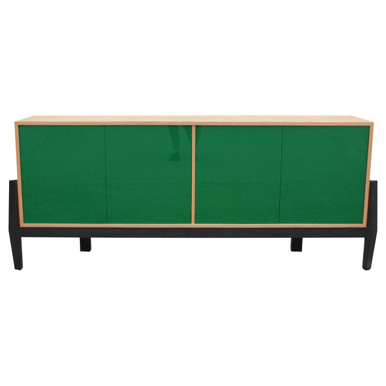 Natural Oak wood credenza or sideboard with four pop out doors. In the interior there are four storage shelves. The green lucite doors are reflective and shiny. The piece was designed by Reeves Design.  Other custom designs can be made including but