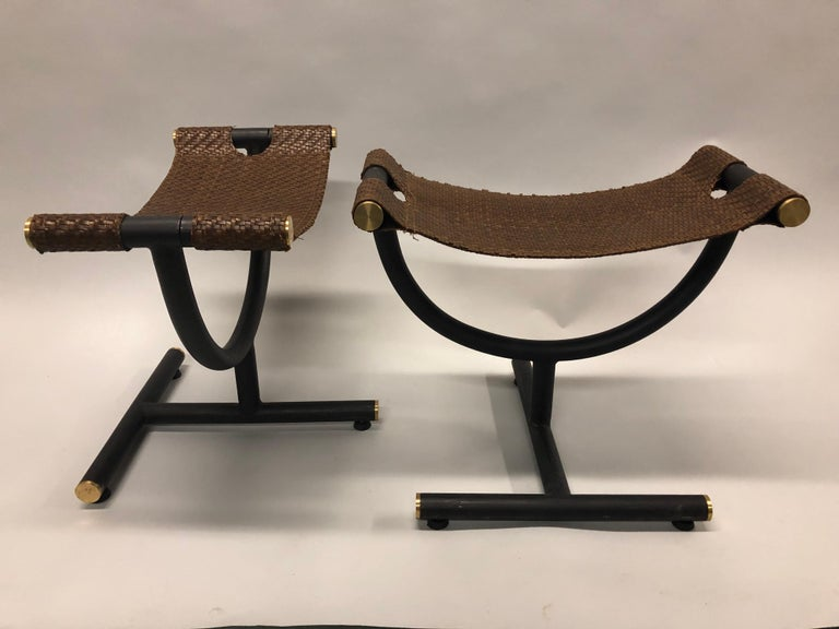 Elegant, custom pair of Italian late 20th century iron and braided leather benches / stools for Gucci  The braided leather seats are cantilevered over an open architectural framework composed of curves and angles and made of black enamel steel
