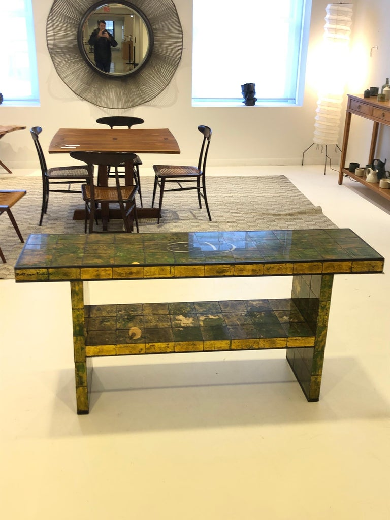 circa 1940, USA, the mosaic tile-clad two-tier table reverse painted in a gold leaf, green and black mottled abstracted design, by artist Karin van Leyden. A rare and elegant collaboration by the legendary Hollywood Society architect-designer and