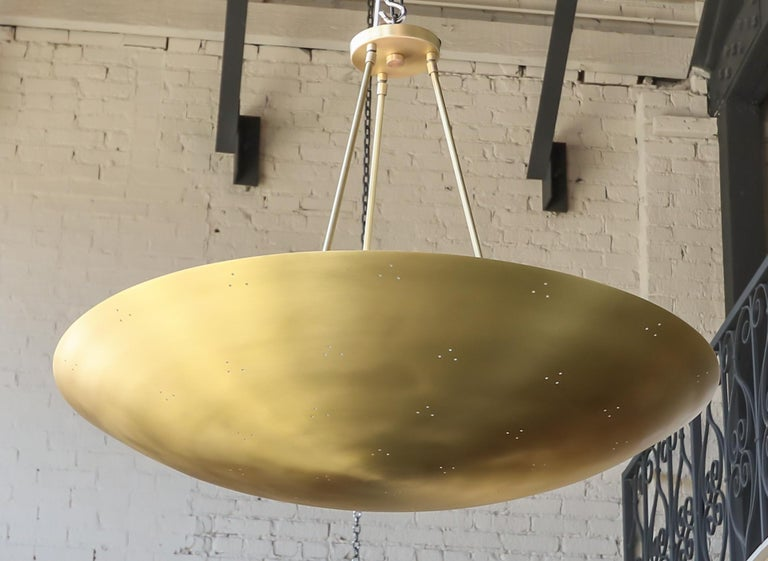 Custom conical /convex shaped pendant chandelier in perforated brass. Can be done in different sizes and finishes.