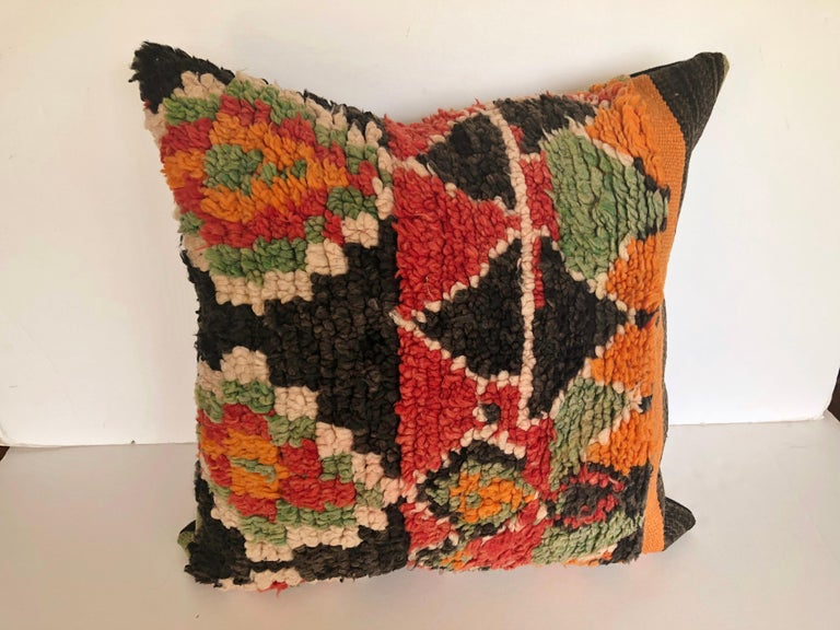 Custom pillow cut from a vintage hand loomed wool Ait Bou Ichaouen Berber rug, one of the most isolated tribes in Morocco. Bold striking colors and patterns reflect an older North African tradition unlike those found elsewhere. Pillow is backed in