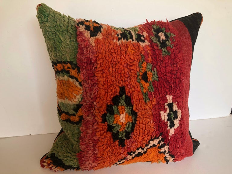 Custom pillow cut from a vintage hand loomed wool Ait Bou Ichaouen Berber rug, one of the most isolated tribes in Morocco. Bold striking colors and patterns reflect an older North African tradition unlike those found elsewhere. The pillow is backed