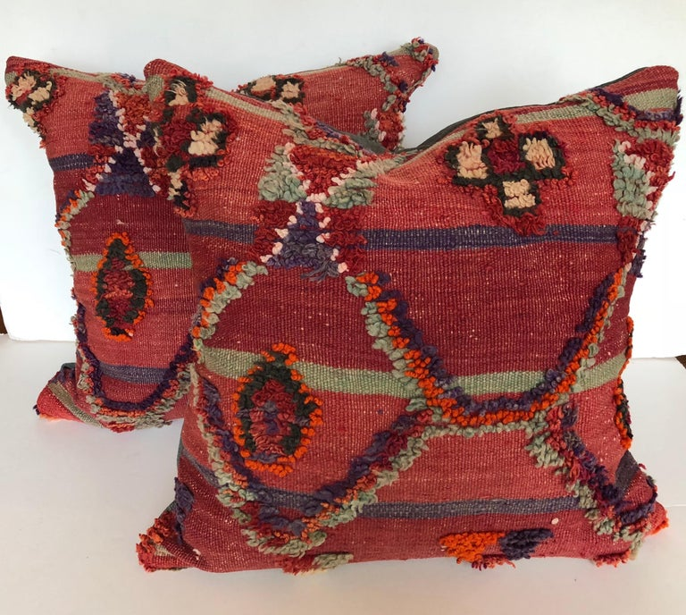Custom pillow cut from a vintage hand loomed wool Ait Bou Ichaouen Moroccan Berber rug, one of the most remote, isolated tribes in Morocco. Bold colors and patterns reflect an older North African tradition unlike those from elsewhere. The pillow is
