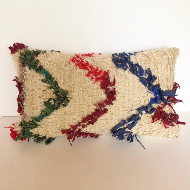 Custom pillow cut from a vintage hand loomed wool Beni Ouarain Moroccan Berber rug from the Atlas Mountains. Wool is soft and lustrous with assorted textile tufted designs. Pillow is backed with a silk blend, filled with an insert of 50/50 down and
