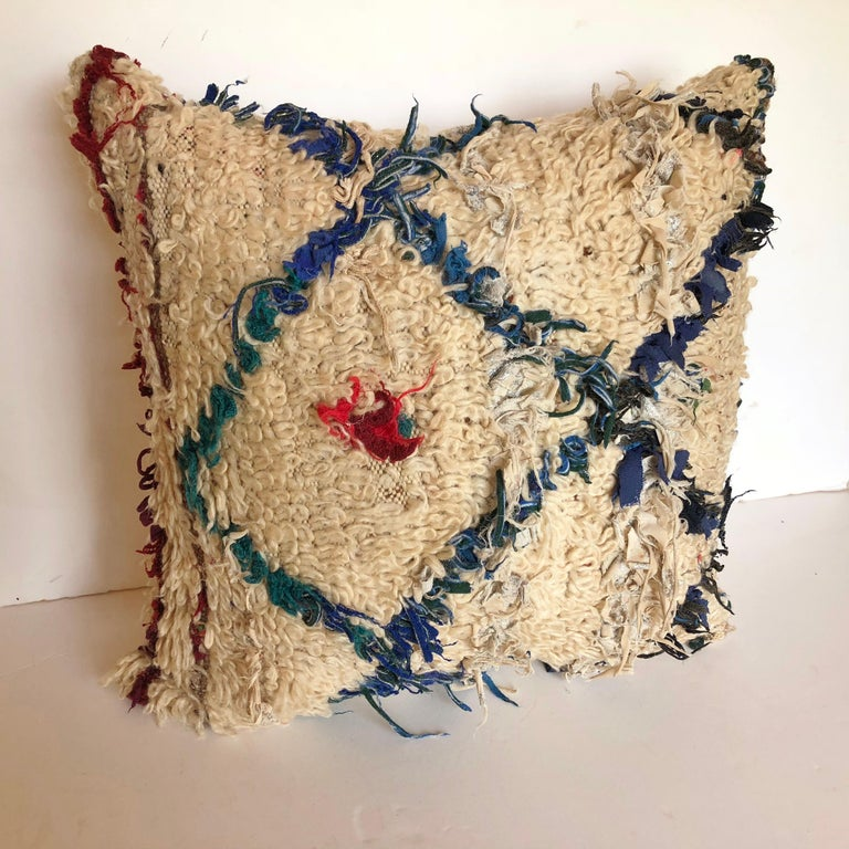 Custom pillow cut from a vintage hand loomed wool Beni Ouarain Moroccan rug from the Atlas Mountains. Pillow is backed in a cream silk blend, filled with an insert of 50/50 down and feathers and hand sewn closed. We make all of our pillows from the