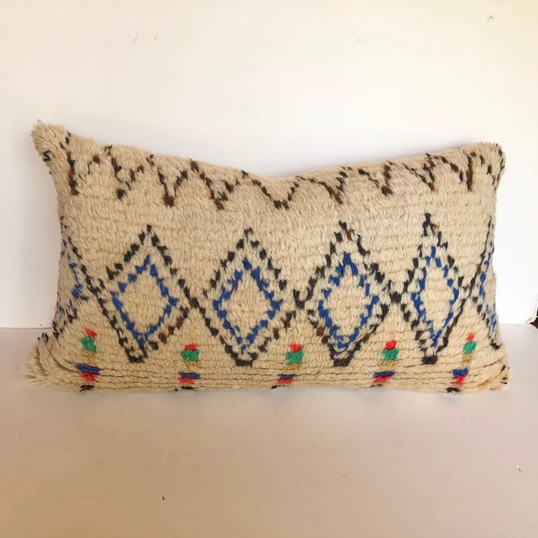 Custom pillow cut from a vintage hand loomed wool Moroccan Azilal rug from the Atlas Mountains. Wool is soft and lustrous with all natural dyes. Pillow is backed in cream mohair, filled with an insert of 100% down and hand sewn closed. We make all