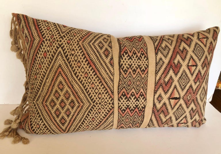Custom pillow cut from a vintage hand loomed wool Moroccan Berber rug from the Atlas Mountains. The pillow incorporates the hand tied fringe that was originally on one end of the rug. It is backed in a silk/linen blend, filled with an insert of