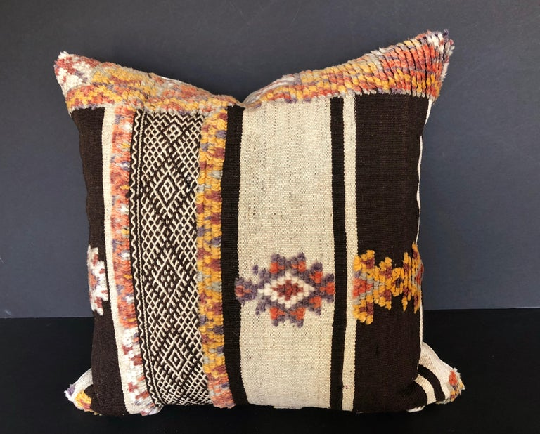 Custom pillow cut from a rare vintage hand loomed wool Moroccan Glaoui rug made by the Berber tribes of the Atlas Mountains. Wool is soft and lustrous with natural dyes. Rlat weave rug is embellished with tufted tribal designs. Pillow is backed with