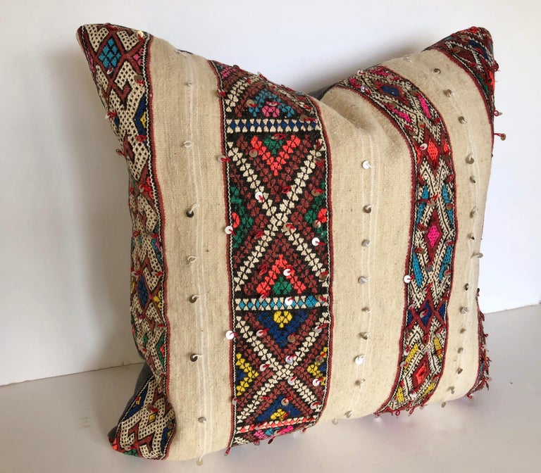 Custom pillow cut from a vintage hand loomed wool vintage Moroccan rug made by the Berber women of the Atlas Mountains. Brightly colored bands are embellished with sequins against a creamy wool textile. Pillow is backed in purple linen, filled with