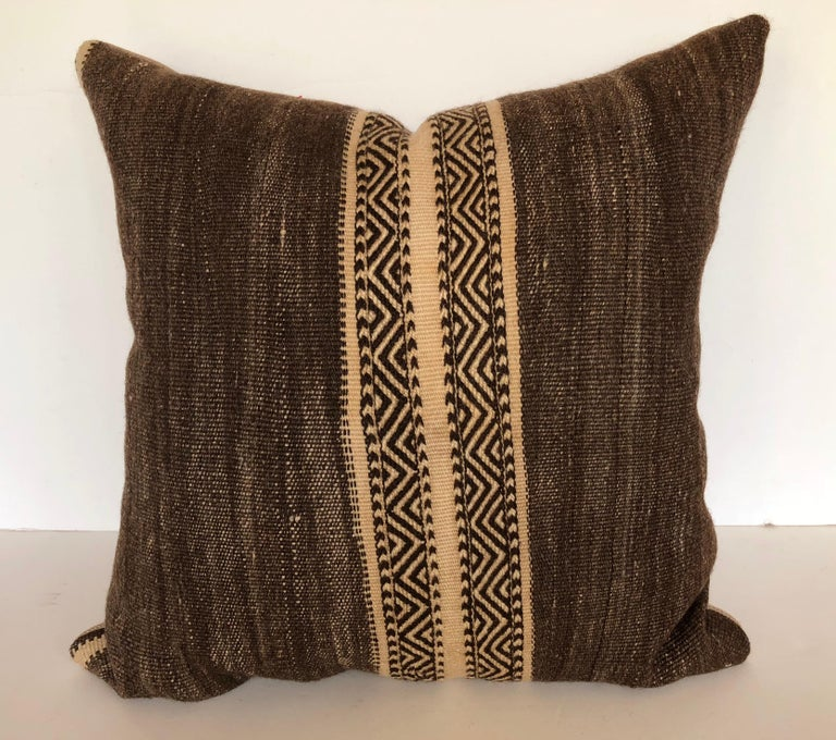 Custom pillow cut from a vintage hand loomed wool Moroccan Kilim rug made by the Berber tribes of the Atlas Mountains. Wool is soft and lustrous with natural color. Pillow is backed in a linen blend, filled with an insert of 50/50 down and feathers