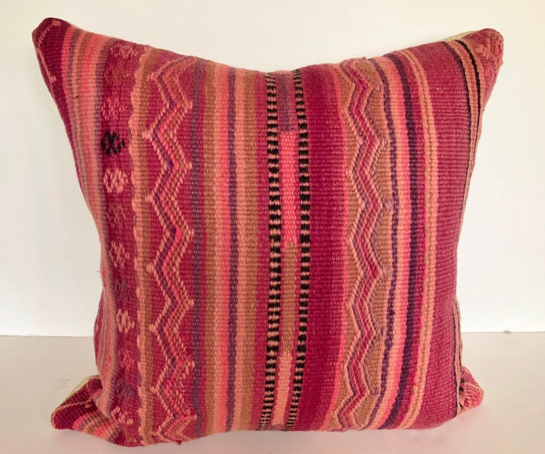 Custom pillow cut from a vintage hand loomed wool Moroccan rug made by the Berber tribes of the Atlas Mountains. Wool is soft and lustrous with natural dyes. The flat-weave stripes are embellished with embroidered tribal designs. Pillow is backed in
