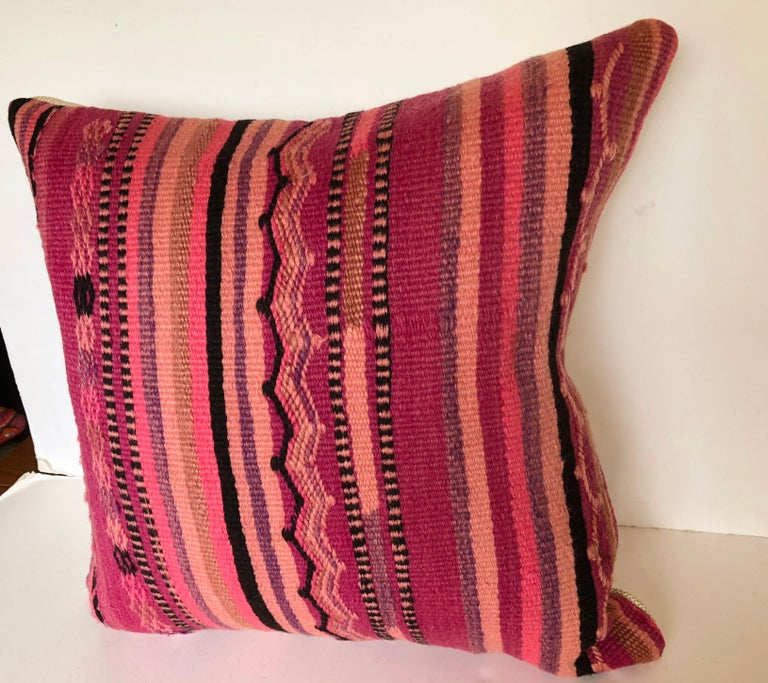 Custom pillow cut from a vintage hand loomed wool Moroccan rug made by the Berber tribes of the Atlas Mountains. Wool is soft and lustrous with natural dyes. Flat-weave stripes are embellished with embroidered tribal designs. Pillow is backed in