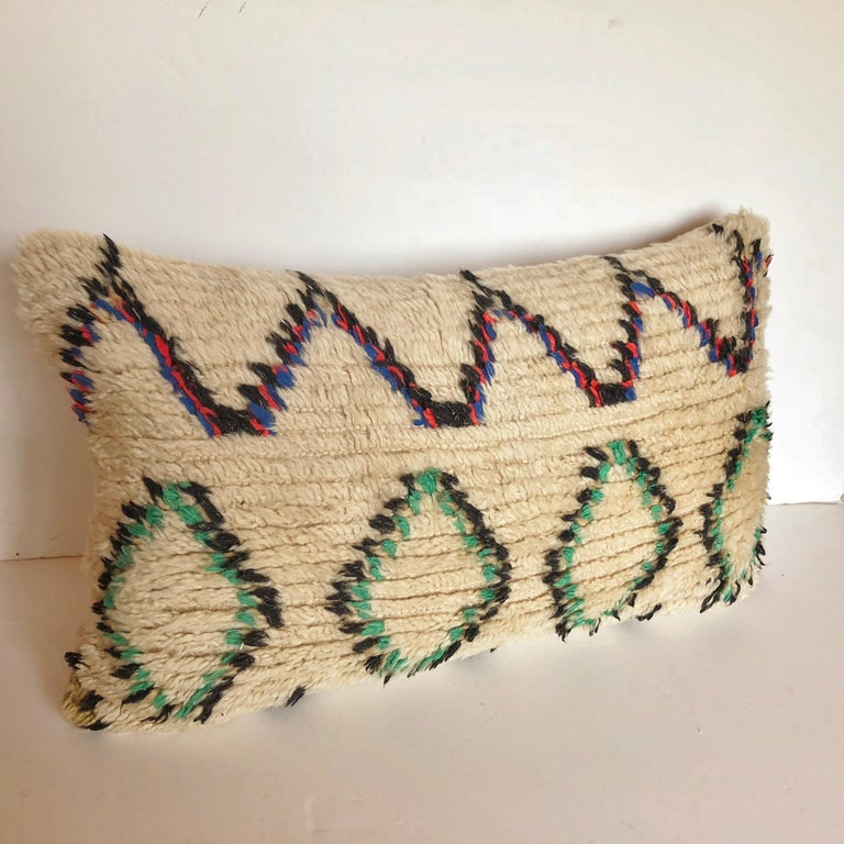 Custom pillow cut from a vintage hand loomed wool Moroccan Azilal rug from the Atlas Mountains. Wool is soft and lustrous with all natural dyes. Pillow is backed in creamy mohair, filled with 100% down and hand sewn closed. We make all of our